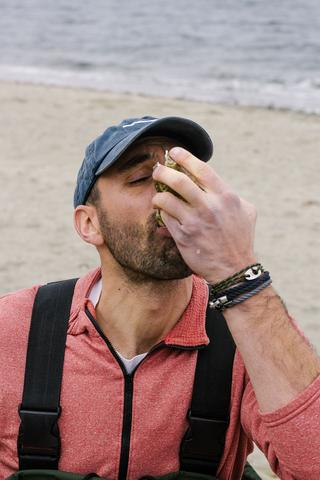 zac eating an oyster on a beach. charger slip knot bracelet and catch double bracelet.