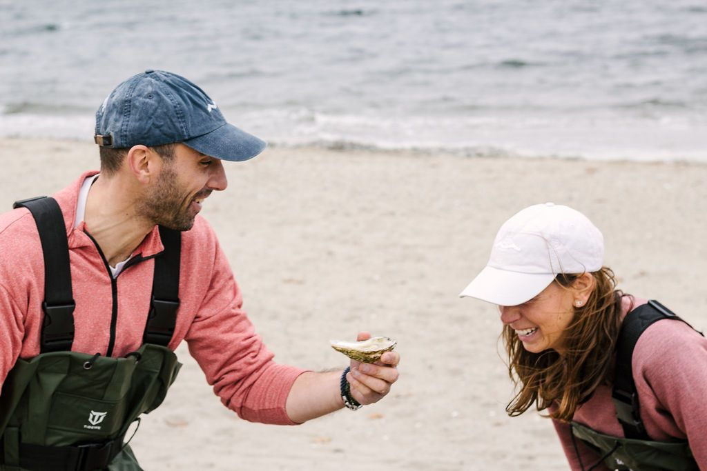 zac and bridget on a beach eating oysters. wearing waders and sailormade hats.